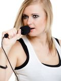 Music. Girl singer musician singing to microphone Stock Photo