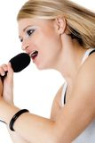 Music. Girl singer musician singing to microphone Royalty Free Stock Photography