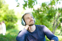 Music in green. Young man with headphones relaxing Stock Photo