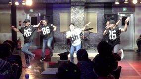 A music group performs in front of Asian ferry passengers in a bar aboard a sea liner.