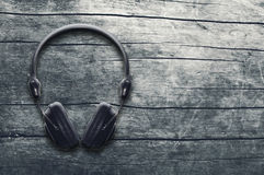 Music grunge background, black headphones on a wooden table Stock Images