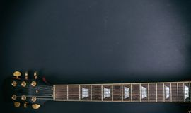 Music, guitar. Top view of a guitar neck fretboard and headstock against black background. Copy space stock photo