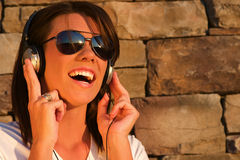 Music Headphones. A cool young woman listens to music on some headphones royalty free stock photography