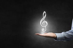 Music icon in hand Stock Photos