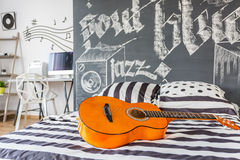 Music inspired bedroom. Shot of a guitar laying on a bed in a black and white music inspired modern bedroom Stock Photography