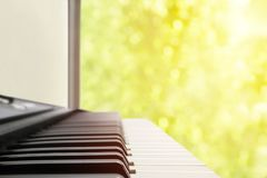 A music instrument background, music concept. A blurred warm color toned photo of electronic keyboard or piano. MIDI synthesizer p Royalty Free Stock Photo