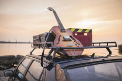 Music instrumental guitar car outdoor background. Vintage musical rusty grunge car luggage rack on the sea shore Royalty Free Stock Images