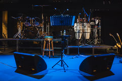 Music instruments on stage in dark studio Stock Images