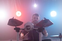 Music, interests, hobby and people concept - young man playing the electronic drums royalty free stock photos
