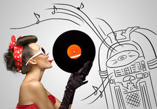 Music from jukebox. Vintage photo of a retro pinup girl licking retro vinyl with her tongue on a sketchy background of a Wurlitzer jukebox Stock Photos