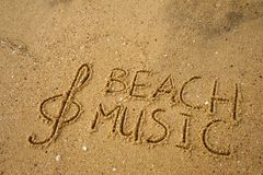 Music key and text beach music drawn on a sand. Music key and text beach music drawn on a yellow sand Stock Image