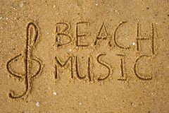 Music key and text beach music drawn on a sand. Music key and text beach music drawn on a yellow sand Royalty Free Stock Photos