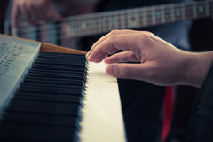 Music keyboard and bass guitar players close up. Hand playing music keyboard and bass guitar player in the background. Detail form a concert stock photos