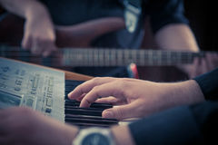 Music keyboard and bass guitar players close up. Hand playing music keyboard and bass guitar player in the background. Detail form a concert royalty free stock images