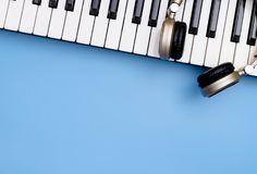 Music Keyboard and Music headphone on blue. Copy space Stock Photo