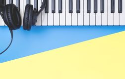 Music keyboard with headphone on blue yellow copy space for Music concept. Music keyboard instrument with headphone on blue yellow copy space for Music concept royalty free stock images