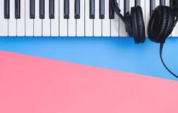 Music keyboard headphone on blue pink copy space for Music poster concept. Music keyboard headphone instrument on blue pink copy space for Music poster concept royalty free stock photo