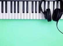 Music Keyboard and headphone on teal. Music Keyboard and Music headphone on teal stock photos
