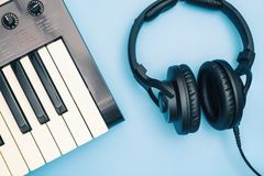 Music keyboard and Music headphone on blue Stock Image