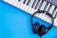 Music keyboard and Music headphone on blue. Copy space Royalty Free Stock Photography