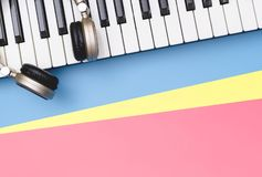 Music keyboard with golden headphone on blue pink copy space. Music keyboard synthesizer with golden headphone on blue pink copy space royalty free stock photo