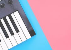 Music keyboard instrument on blue pink copy space. Music keyboard synthesizer instrument on blue pink copy space stock image