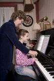 Music Lesson - Vertical. A happy senior woman instructing her young student at the piano royalty free stock image