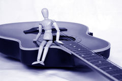 Music lessons. Doll sitting on a guitar royalty free stock image