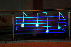 Music light. Music symbols written with light sparkles at night time in an alley way on a wire fence royalty free stock photos