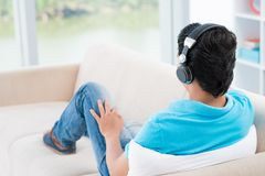 Music listener. Back view of a man in headphones inside Stock Image