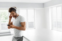 Music Listening. Man In Headphones Using Mobile Phone Indoors. Music Listening. Portrait Of Handsome Muscular Happy Man In Fashion Headphones Using Mobile Phone stock images