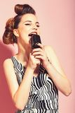 Music, look and retro style, pinup. Pin up young girl on pink background, radio. Girl in glasses sing in microphone. Beauty and vintage fashion. Woman singer royalty free stock photo