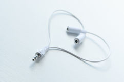 Music Love. A pair of earphone connectors to share made into a heart shape Royalty Free Stock Photo