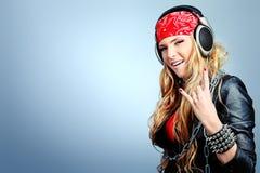 Music lover. Portrait of happy girl listening a music in headphones. Studio shot over grey background Stock Image