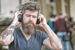 Music lover concept. Man with long beard and mustache with wireless headphones on head, defocused urban background. Hipster with headphones on relaxed face stock image