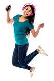 Music lover jumping high in the air Royalty Free Stock Image