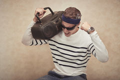 Music lover. Man with headband listening to music in his boombox stock images