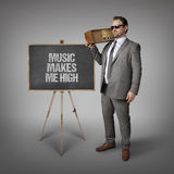Music makes me high text on blackboard with businessman Royalty Free Stock Photography