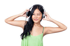 Music makes me silly. A young Asian girl looking towards a headphone with a funny face Stock Photo