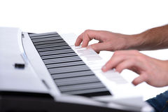 Music. Male hands playing digital piano. Isolated over white background Royalty Free Stock Photography