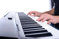 Music. Male hands playing digital piano. Isolated over white background Stock Images