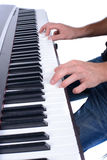 Music. Male hands playing digital piano. Isolated over white background Royalty Free Stock Images