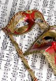 Music Mask 1. Two masks lay on top of a score of complicated music. Musical love Royalty Free Stock Photos