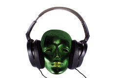Music Mask. An antique green mask hearing music on the headphones Royalty Free Stock Photography