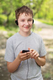 Music with me. The boy in headphones listens to music in park Royalty Free Stock Photography