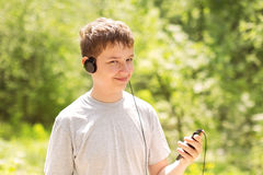 Music with me. The boy in headphones listens to music in park Stock Photos