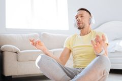 Wistful concentrated man enjoying mediation. Music for meditation. Inspired creative smart man finding inner balance while concentrating on thoughts and relaxing Stock Photography