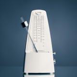 Music metronome. With moving pendulum against blue background, studio shot Stock Photos