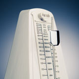 Music metronome. With moving pendulum against blue background, close-up view stock photography