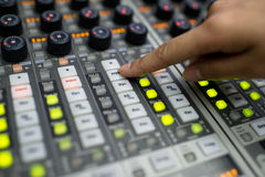 Music Mixer. Audio division is operating a digital mixer button Royalty Free Stock Photography
